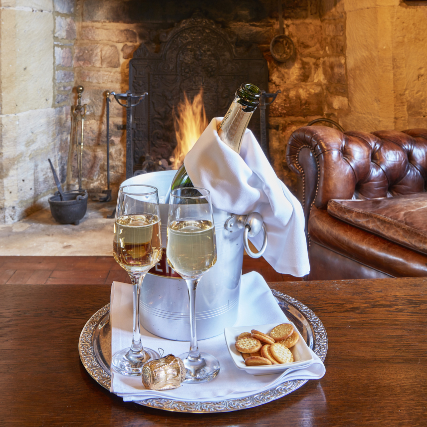 Bucket of Champagne on ice, with two filled glasses and small plate of biscuits