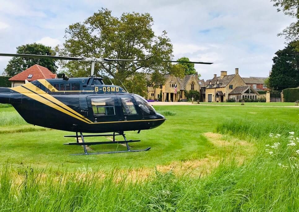 Helicopter landed on helipad with Abbots Grange in background